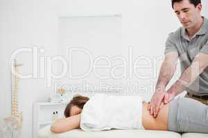 Masseur massaging the back of a brunette woman