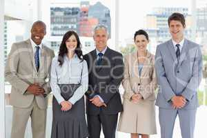 Smiling business team standing upright side by side with their h