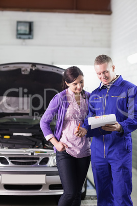Mechanic showing a paper in a clipboard to a client