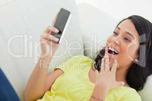 Close-up of a surprised Latino woman  looking her smartphone