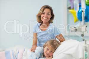 Child lying on a medical bed next to his mother