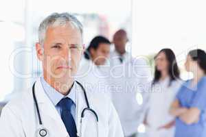 Mature doctor looking straight ahead while his team is looking a