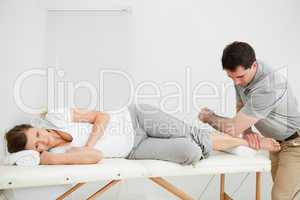 Doctor manipulating the leg of his patient while using his elbow