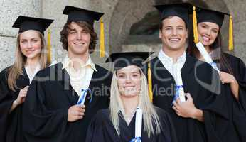 Close-up of five happy graduates posing