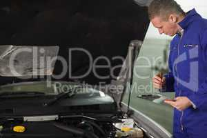 Mechanic looking at a car engine while holding a clipboard