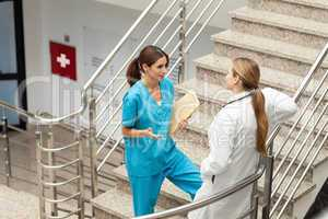 Nusre and doctor talking in a stairwell