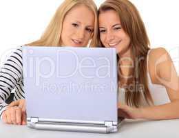 Zwei junge Frauen sitzen gemeinsam vor Notebook