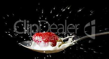 red, ripe strawberry falling in spoon with milk