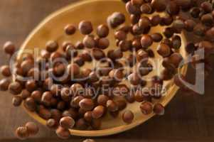 Hazelnuts in Motion Tumbling into Bamboo Bowl