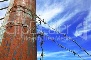 barbed wire on the pole against the blue sky