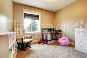 Nursing room for baby girl with brown wood crib.