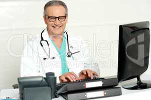 Aged male doctor in glasses working on computer