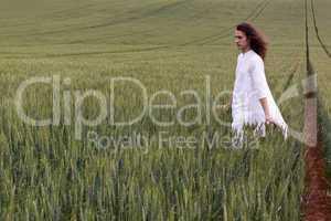 Spiritual daydreamer striding through a cornfield