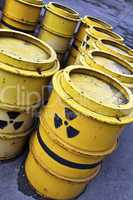 Radioactive warning symbol on yellow tuns of toxic waste