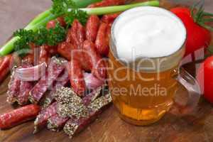 mug of beer and an assortment of salami and vegetables on a cutt