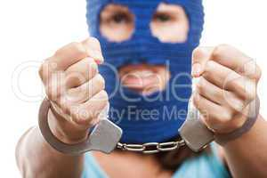 Woman in balaclava showing handcuffs on hands