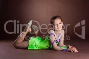 Young teen girl in green gymnast costume posing