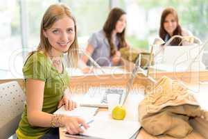 Smiling teenage girl sitting at study room