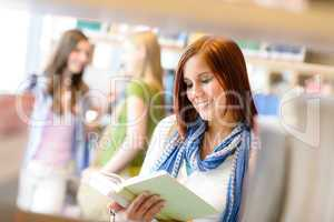 Teenage woman read among book shelves library