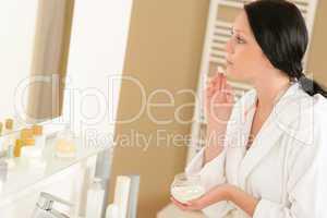 Woman apply face cream looking bathroom mirror