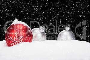 christaumkugeln im schnee bei schneefall