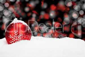 rote christbaumkugel im schnee