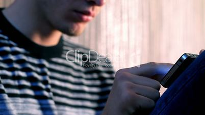 young adult man using touchscreen phone.