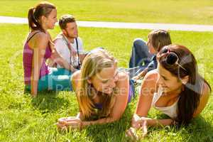 Teens talking relaxing on grass in park