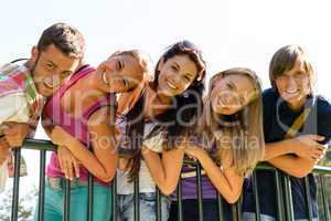 Teens having fun in park leaning fence