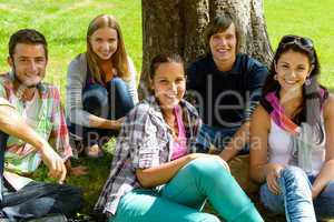 Students relaxing on meadow in park teens