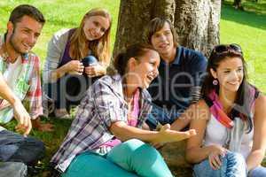 Students relaxing in schoolyard teens meadow park