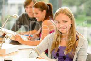 High-school student taking notes in study room