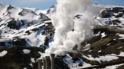 Steam rising from a geothermal electrical company in Iceland with snowcovered mountains in the background.
