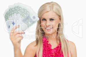 Fair hair woman holding 100 euros banknotes