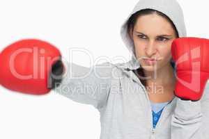 Combative brunette in sweatshirt boxing