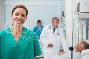 Smiling nurse standing in a hospital room