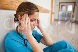 Nurse sitting on the floor hands on head