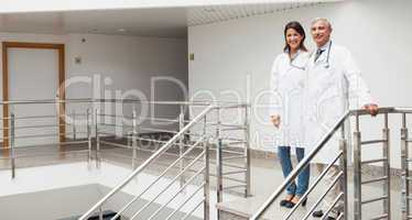 Two doctors standing at top of stairs