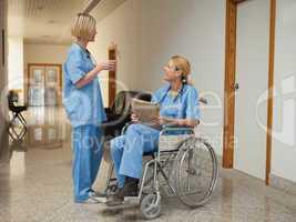 Nurse with drink talking to nurse in wheelchair with folder