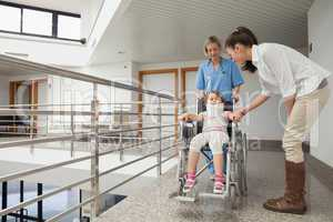 Nurse pushing child in wheelchair with mother