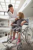 Doctor talking to child with neckb race in wheelchair