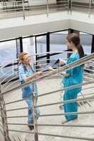 Nurse handing folder to other nurse