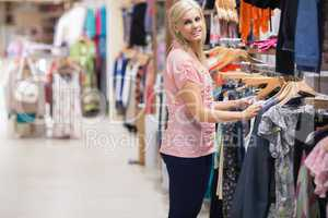 Woman is smiling by the clothes rail