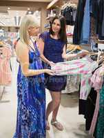 Women standing at a clothes rail and smiling