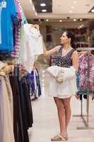 Woman holding white shirts on hangers