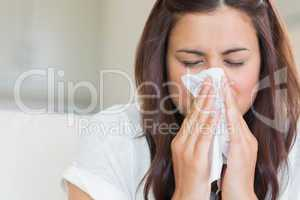 Brunette blowing nose into tissue