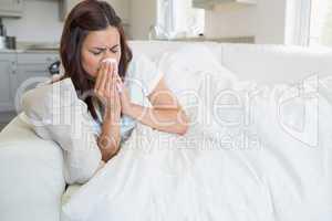 Brunette feeling ill on sofa