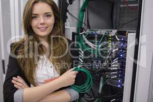 Girl holding cable in front of rack mounted servers