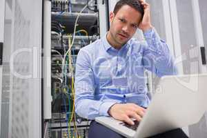 Technician getting frustrated with laptop over servers