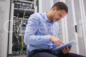 Man using tablet pc beside servers
